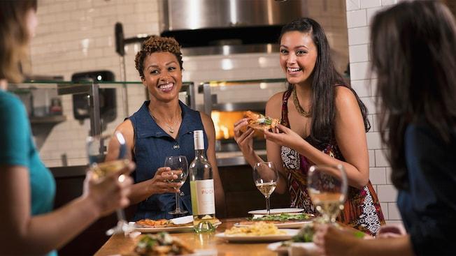Dos amigas disfrutan pizza artesanal y vino