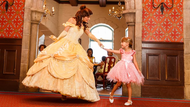 Princess Belle dances with a girl dressed as a princess