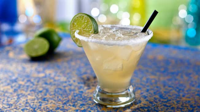 A margarita on the rocks with a lime wedge and salt around the rim of the glass