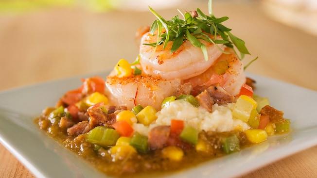 Un plato con ensalada verde sobre camarones jumbo sobre una base de maíz y verduras picadas