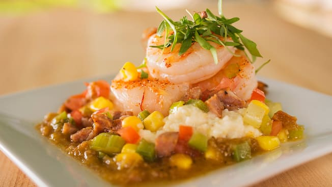 A dish with greens atop jumbo shrimp on a bed of corn and chopped vegetables