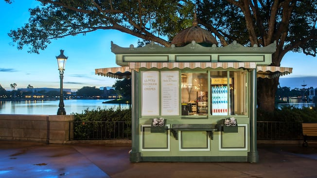 A quaint kiosk featuring Crepes des Chefs de France glows under the evening sky as dusk approaches