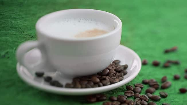 A foamy cup of cappuccino from STARBUCKS® plated beside a scattered array of espresso beans