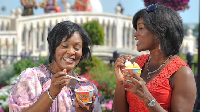 Epcot dining guide: Two women enjoy eating gelato at the Gelati kiosk in the Italy Pavilion at Epcot