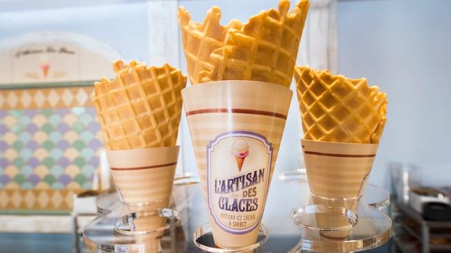 Tres conos de waffle vacíos de L'Artisan des Glaces sobre el mostrador de servicio