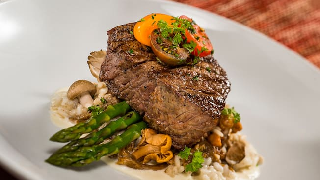 Filet mignon sitting on a bed of asparagus and a mushroom risotto with a white truffle butter sauce