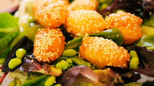 Ensalada de pollo y sésamo, con pollo a la naranja servido sobre un colchón de hojas verdes y frijoles edamame