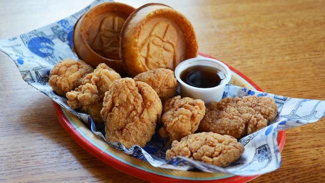 Un plato lleno de bocaditos de pollo, 2waffles con la cara de Darth Vader y un acompañante de sirope de arce