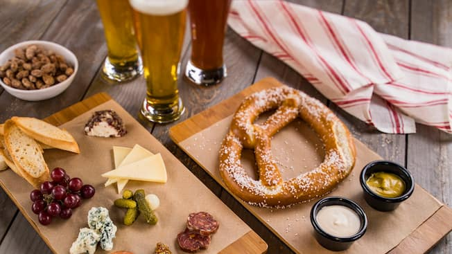 A charcuterie board, a bowl of nuts and a pretzel with dipping sauces next to 3 glasses and a cloth napkin