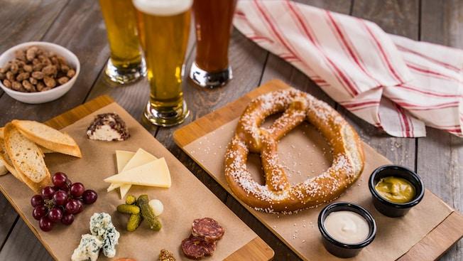 Una tabla de fiambres, un tazón de nueces y un pretzel con salsas para mojar junto a 3vasos y una servilleta de tela