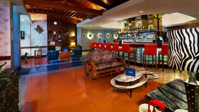 sala inspirada en la década de 1950 con televisores blanco y negro y un asiento rojo brillante en el mostrador