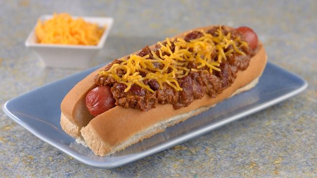 Un hot dog cubierto con chile y queso cheddar rallado en un plato, cerca de otro plato con queso cheddar