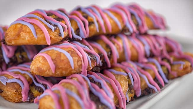 A stack of several pastries drizzled with brightly colored icing