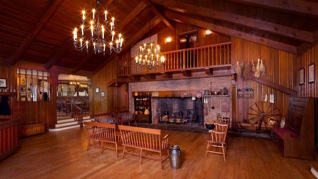 Hall de espera inspirado en la época colonial de los Estados Unidos, con chimenea de piedra, bancos y lámparas chandelier