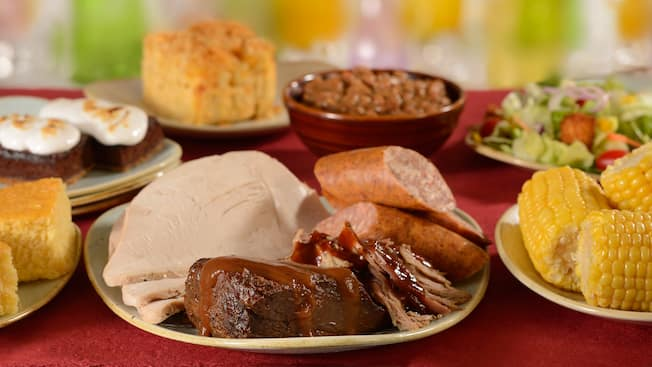 A plate containing sliced turkey, beef brisket with gravy and sliced sausage links is surrounded by several smaller dishes containing, respectively, a square of cornbread, a marshmallow topped smores brownie, a biscuit, baked beans, a mixed green salad and corn on the cob pieces