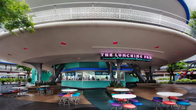 Colorful stools, tables and neon sign outside The Lunching Pad restaurant in Tomorrowland