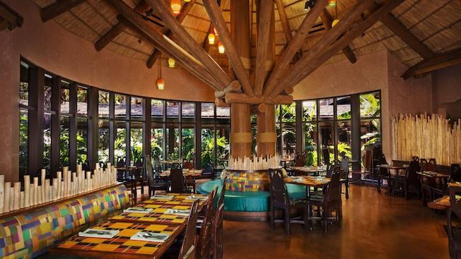 Área de refeições no Boma — Flavors of Africa, com uma cobertura de palha e janelas panorâmicas com vista para o jardim