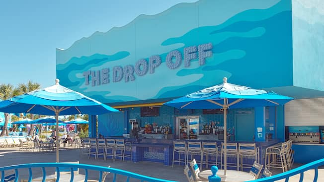 Mesas con sombrillas y sillas de bar cerca del bar de piscina The Drop Off, en Disney's Art of Animation Resort