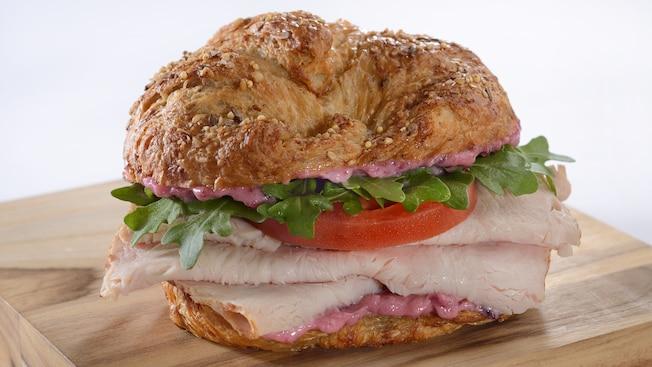 Um sanduíche de croissant multigrãos recheado com peru, rúcula e tomate
