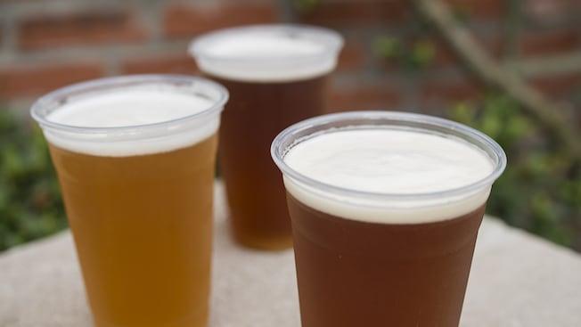 Varios vasos llenos de diferentes cervezas heladas con espuma hasta el borde