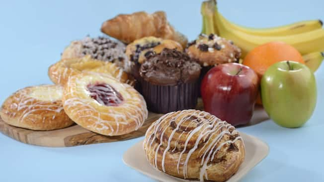 Una variedad de ingredientes de un desayuno continental, incluidos panecillos de canela, panecillos daneses de queso, muffins y fruta