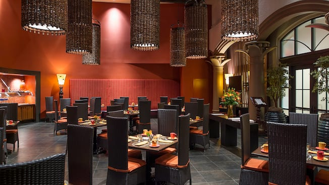 Wicker lanterns hanging from the ceiling while illuminating the vibrant dining space at Las Ventanas