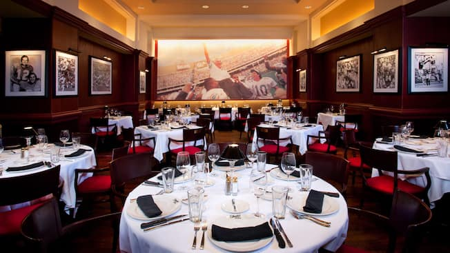 Wood-paneled dining area with a long table set for dinner at Shula's Steak House