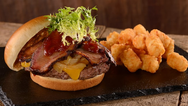 A hamburger topped with cheese, onions, a meat patty, sliced brisket and lettuce next to a pile of tater tots