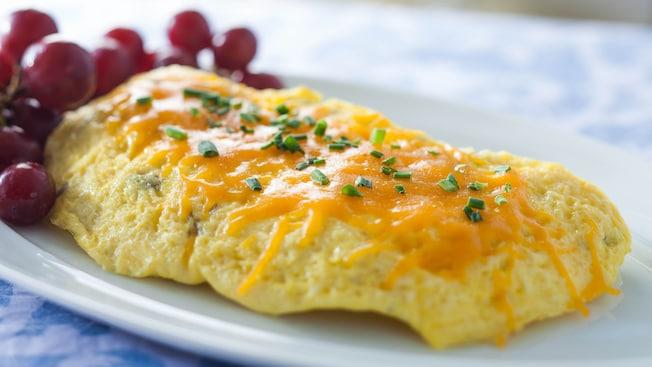 Omelette garnie de cheddar fondu et de ciboulette accompagnée de raisins rouges