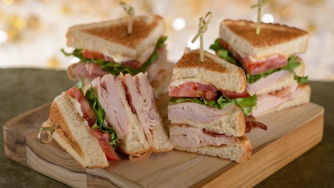Un club sandwich à la dinde, divisé en 4sections, chacune retenue par un cure-dent, est servi sur une planche de bois