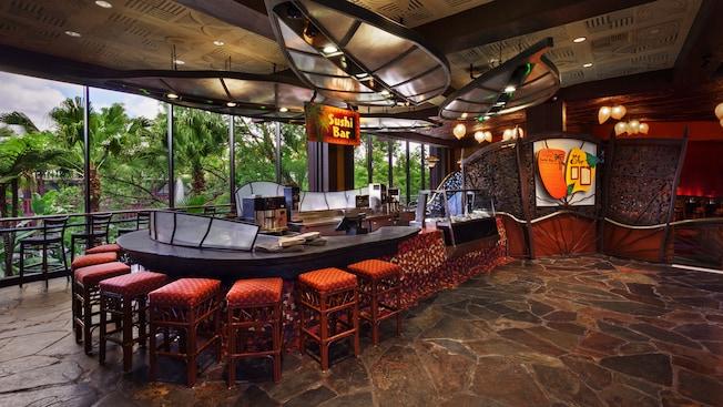 Sushi bar curvo com bancos, ao lado das janelas do chão ao teto com vista das palmeiras