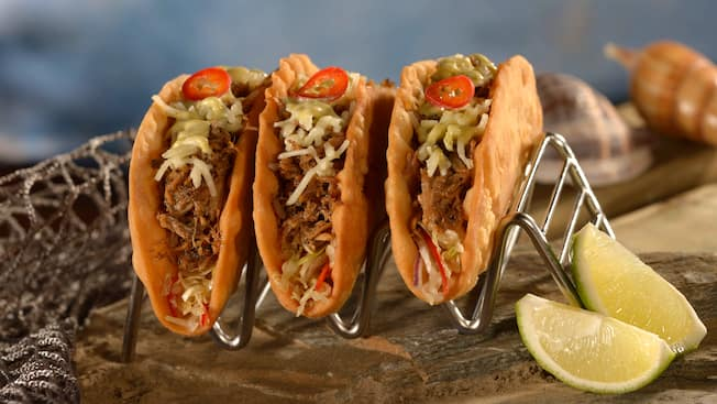 A trio of Kahlua pork tacos served inside crispy shells and garnished with a side of sliced limes