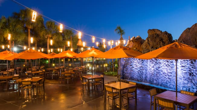 Hanging lanterns, palm trees and a waterfall surround an outdoor patio with tables and chairs lit up at night