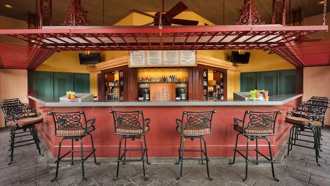 Bar de piscina al aire libre con taburetes de hierro forjado, piso empedrado y ventiladores de techo