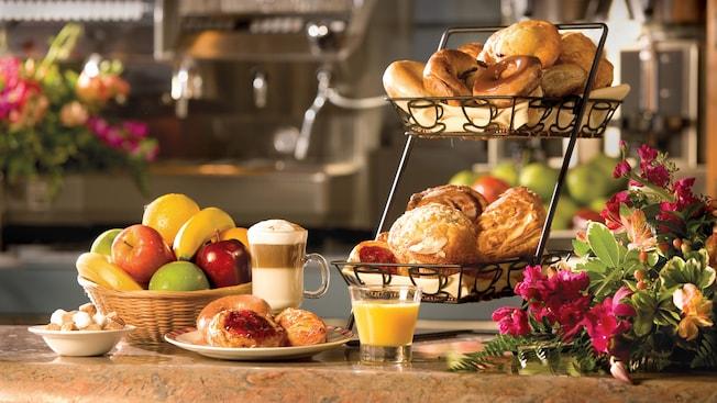 Um copo de suco de laranja e uma xícara de cappuccino ao lado de cestas de frutas, pães e bolos