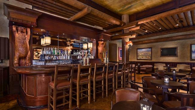 La sala de estar inspirada en la frontera del Oeste se asemeja a una taberna de antaño con pinturas de alces en las paredes y osos tallados en madera flanqueando la barra