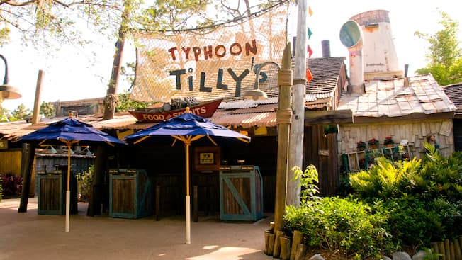 "Entrada a un restaurante de servicio rápido, con 2 sombrillas en el patio y un letrero sobre la red que dice ""Typhoon Tilly's, Food and Spirits"""