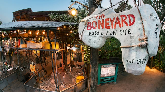 A bone-shaped sign identifies the Boneyard Fossil Fun Site in front of a shack with corrugated roofing