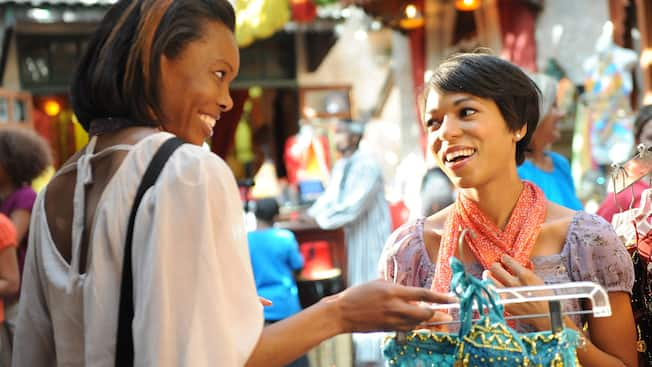 In a middle eastern bazaar setting, 2 women share a laugh as one holds up a 2 piece beaded Jasmine costume on a hanger