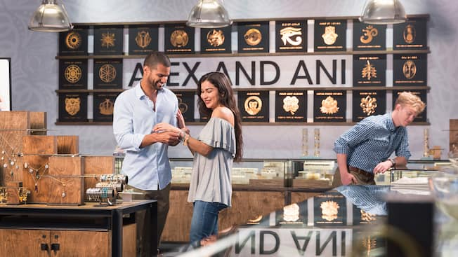 The interior of ALEX and ANI with a man adjusting a bracelet on his girlfriend's wrist and a man peering into a counter display