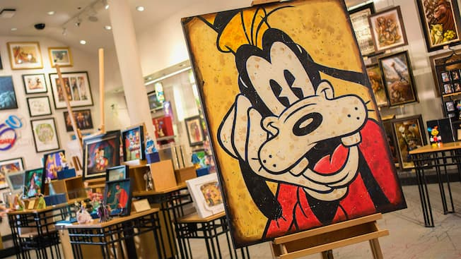 A piece of artwork featuring Goofy on display on an easel