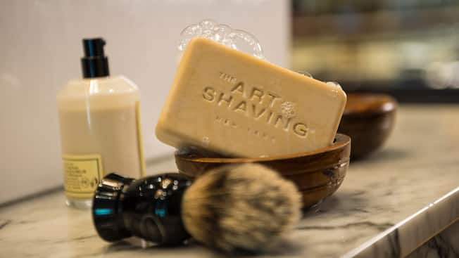 Grooming products at The Art of Shaving shop featuring a shaving brush, soap, wooden bowl and balm