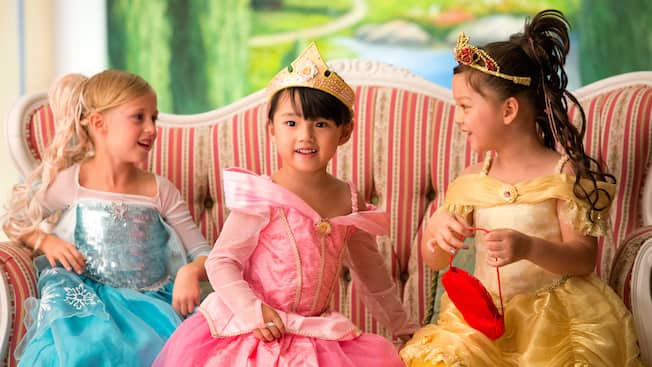 3 las niñas se sientan en un sofá vestidas con su traje de princesa completo