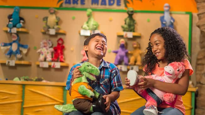 A boy and a girl laugh as they each hold a plush dinosaur toy
