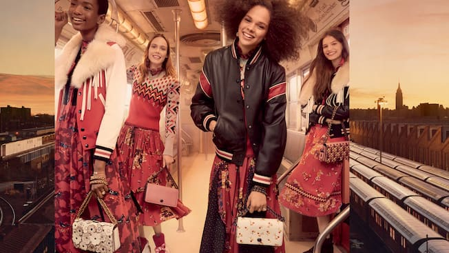 Four women carry Coach handbags and stand inside a train car