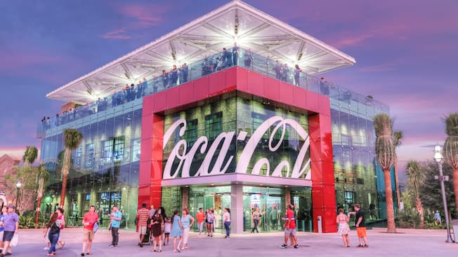 An artist rendering of the exterior of the Coca Cola Store with Guests enjoying the rooftop beverage bar