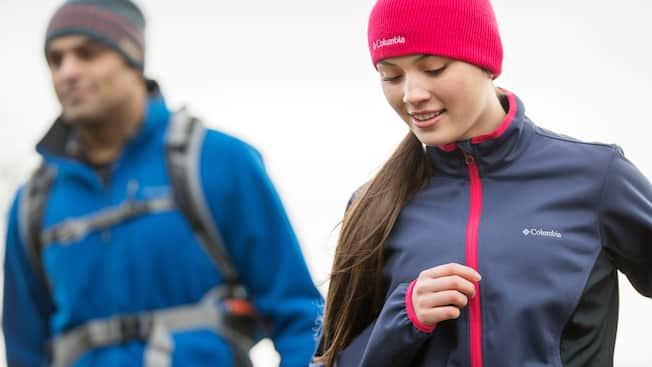 A man and a woman dressed in cold weather hiking apparel by Columbia Sportswear