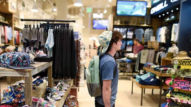 Un niño con una gorra y una mochila mira ropa en Curl by Sammy Duvall