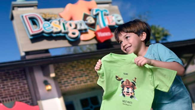 A little boy holds up his custom made T shirt outside of the Disney Design a Tee store