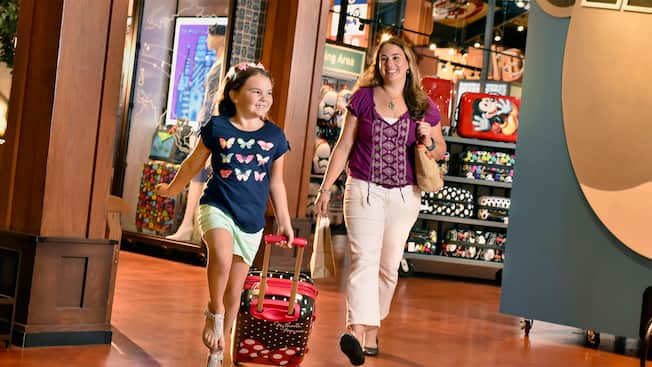 A girl pulls a Minnie themed suitcase inside the Disney Tag boutique as her mother walks alongside her